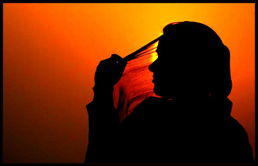 A woman adjusts her scarf as the sun sets over Kashmir's Dal Lake in Srinagar