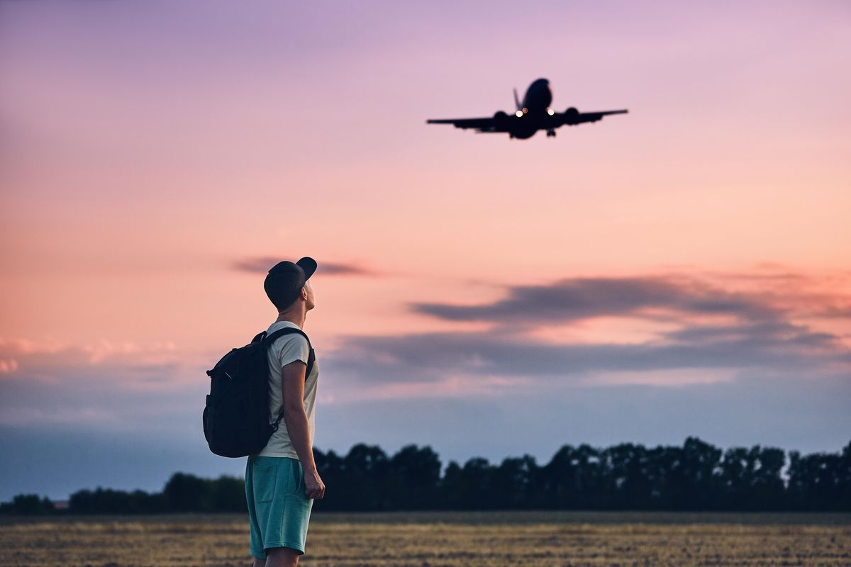 Image of a tourist looking at an airplane take flight