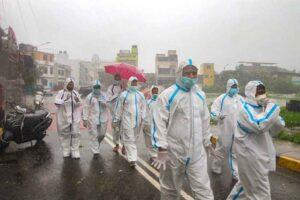 covid health workers walk in rains