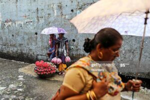 Flower vendors take shelter from the rain under an umbrella
